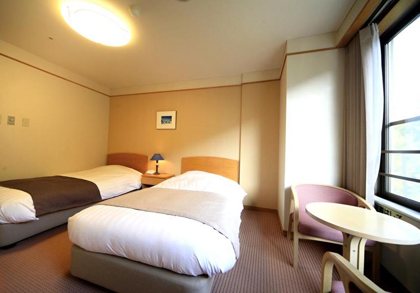 畳敷きの客室(布団付)とカーペットフロアの洋室(ベッド付)を用意しています。各客室に薄型テレビ、お茶セット、冷蔵庫、専用バスルームが備わります。